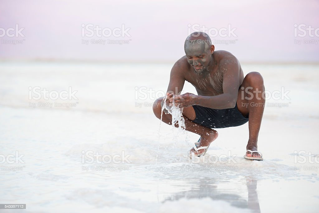Man enjoying vacation on Dead Sea beach. stock photo