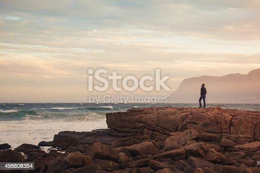 istock Man enjoying view of wavy ocean during sunset (South Africa) 498808354