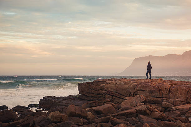 Man enjoying view of wavy ocean during sunset (South Africa) stock photo