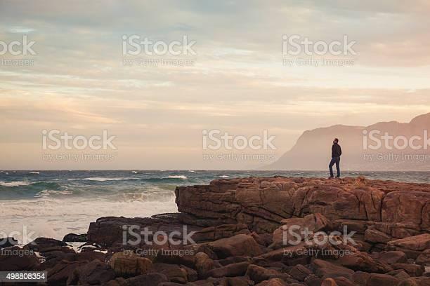 Photo of Man enjoying view of wavy ocean during sunset (South Africa)