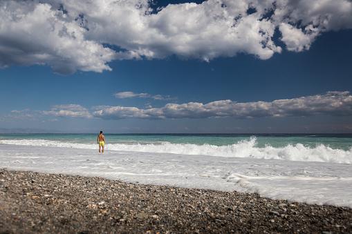 Man enjoying waves in Spiaggia San Marco near Taormina, Sicily