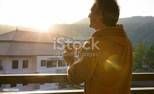 Man enjoys hot drink, on jungle railing, at sunrise