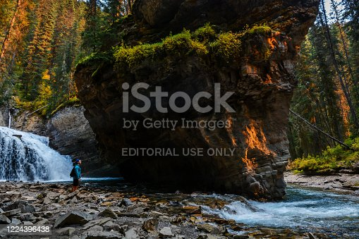 A man enjoy the scenery at one of the waterfalls along the Johnston Canyon hike at Banff National Park in Alberta, Canada. The evening sunlight is red after being filtered though smoke from a nearby forest fire.