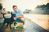 Young man enjoys spending time together with his dog outdoors