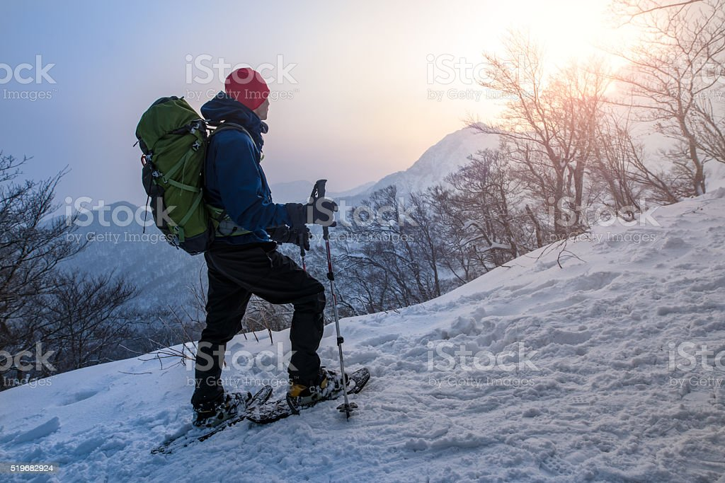 Man enjoys sunrise while snowshoeing through a forest stock photo