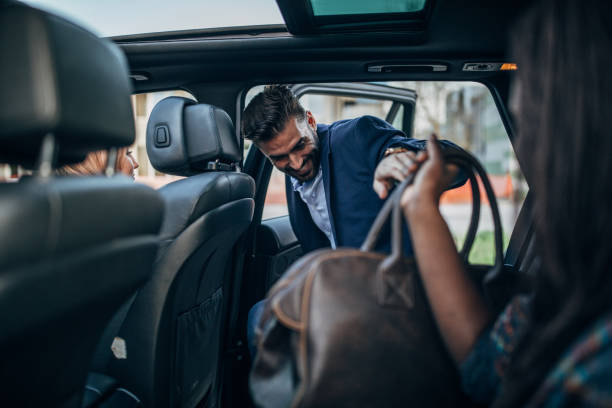 Man entering a ride sharing car Multi-ethnic group of people in a car together, ride sharing in city, entering stock pictures, royalty-free photos & images