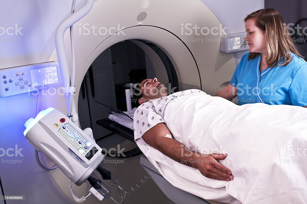 Man entering CAT scan overseen by nurse stock photo
