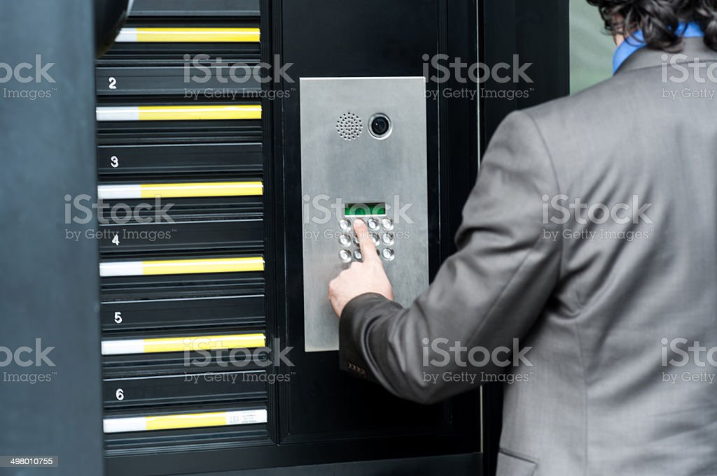 Man entering security code to unlock the door stock photo