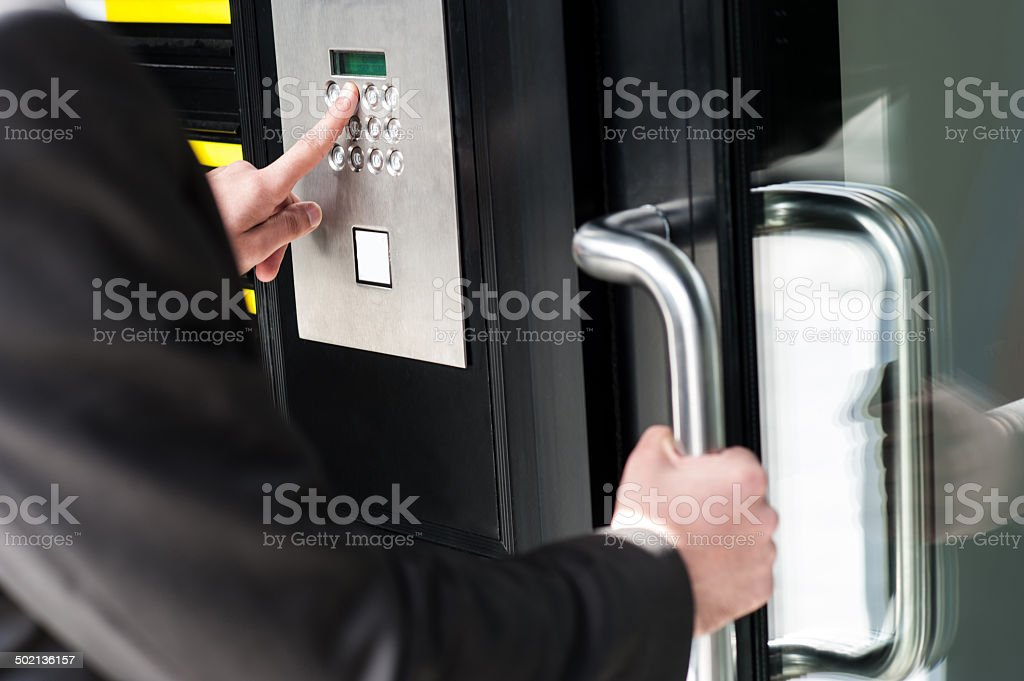 Man entering security code to unlock the door stock photo