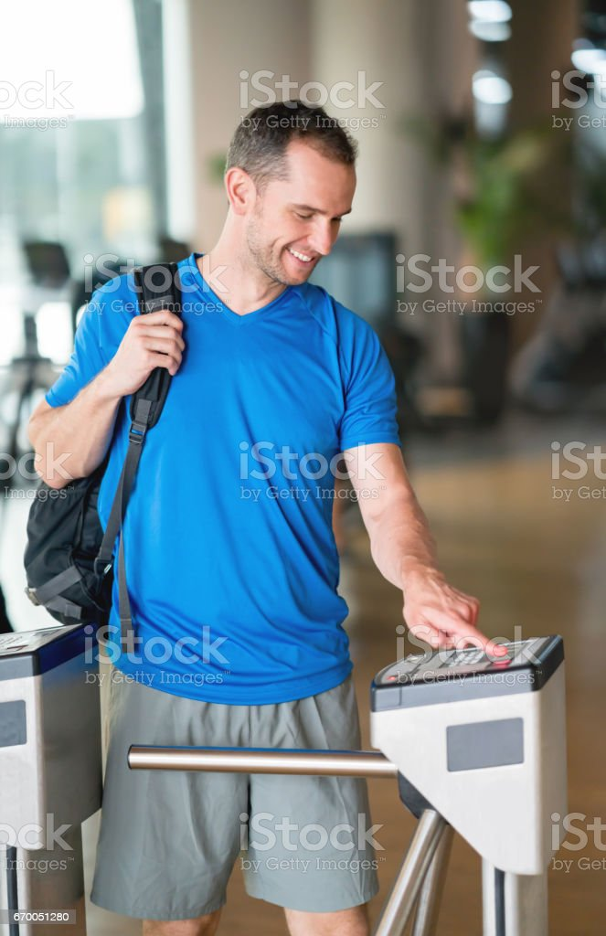 Man entering the gym with a fingerprint scan stock photo