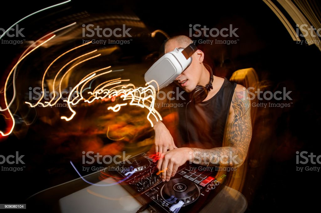 Man enthusiastically plays on the DJ mixer against stock photo