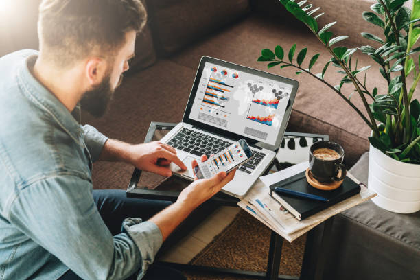 man, entrepreneur, freelancer sits at home on couch at coffee table, uses smartphone, working on laptop with graphs - digital marketing stock pictures, royalty-free photos & images