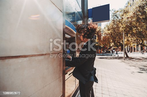 istock Man entrepreneur is using street ATM 1086952672