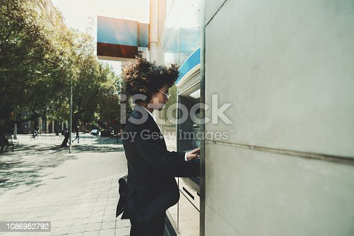 istock Man entrepreneur using ATM outdoors 1086952792