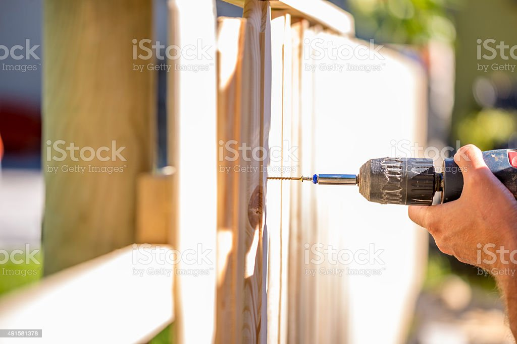 Man erecting a wooden fence outdoors stock photo