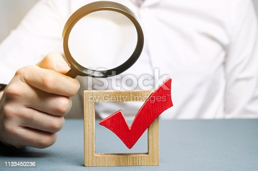 istock A man examines a red check mark through a magnifying glass. Assessing the transparency of the legitimacy of an election or referendum. Illegal Anex, falsifications and violations. Democracy. 1133450236