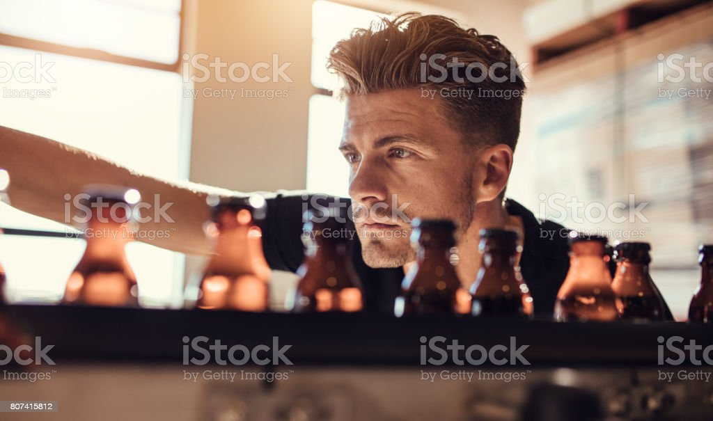 Man examining the beer bottles on conveyor at brewery factory stock photo