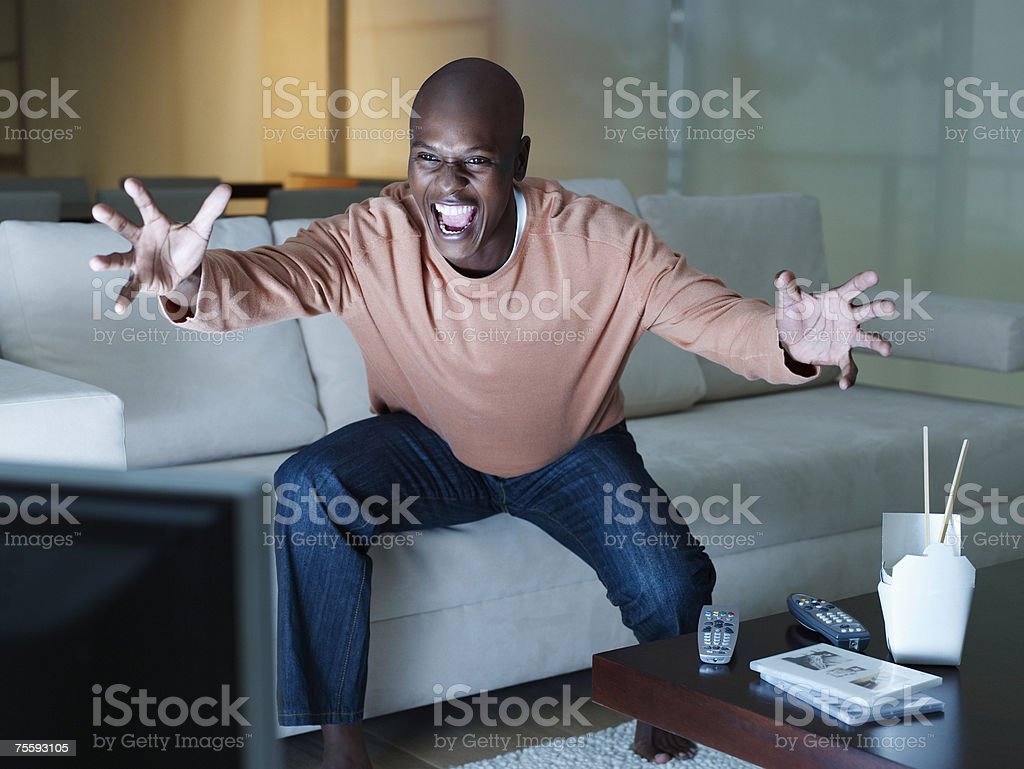 Man excitedly watching the television stock photo