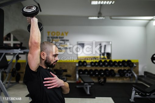 Man exercises triceps with dumbbell