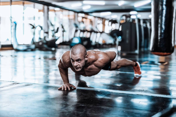 man exercising and doing push-ups in the local gym - milan2099 stock photos and pictures