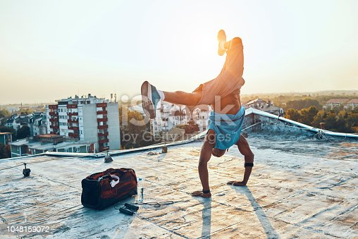 athletic and acrobatic man doing a hand stand on the roof