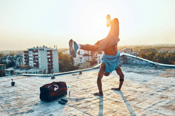 man exercising and hand standing on the rooftop stock photo