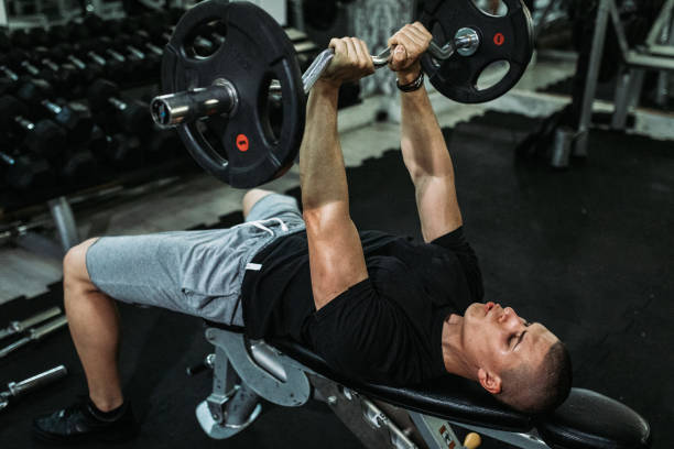 Man exercising and lifting weights in the gym stock photo