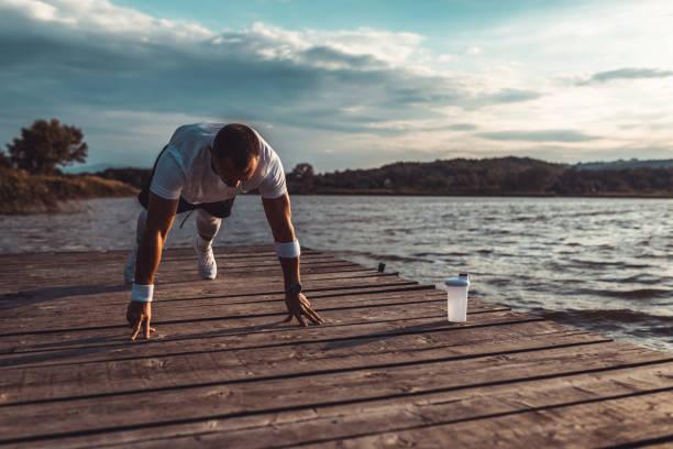 Man exercising at the dock of a lake stock photo