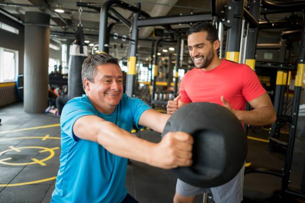 Hombre haciendo ejercicio en el gimnasio con un entrenador personal - foto de stock