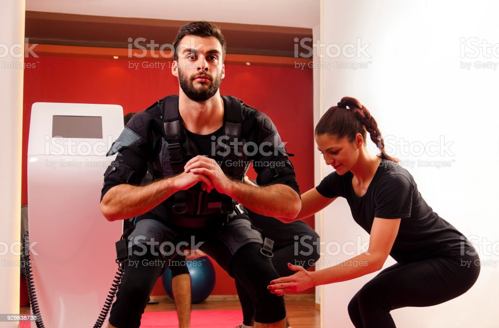 Man exercising attached to EMS , female personal trainer explaining...