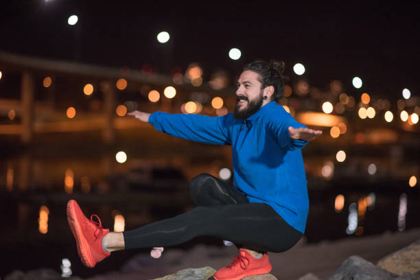 Man exercising balance outdoors at night Male jogger  exercising at night man bun stock pictures, royalty-free photos & images
