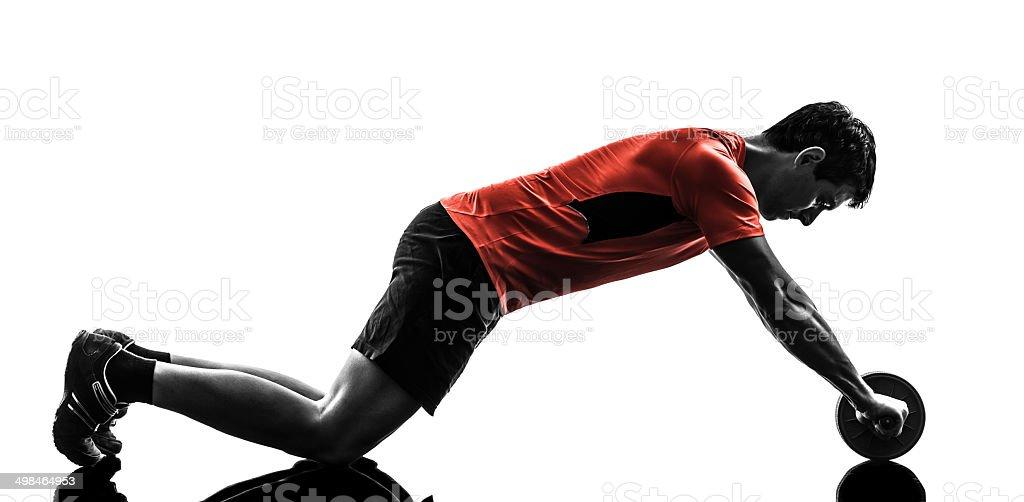 man exercising fitness workout abdominal toning wheel silhouette stock photo