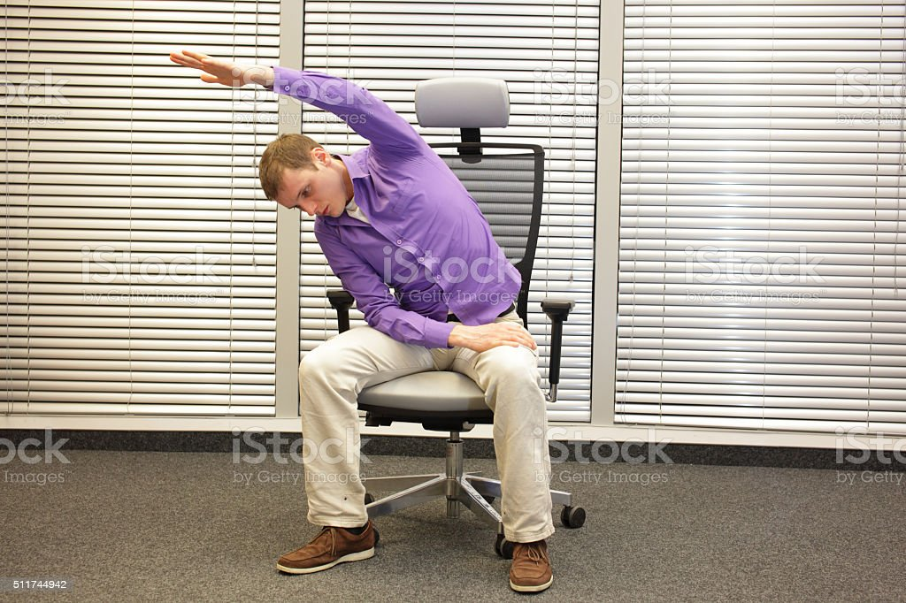 man exercising on chair in office, healthy lifestyle stock photo