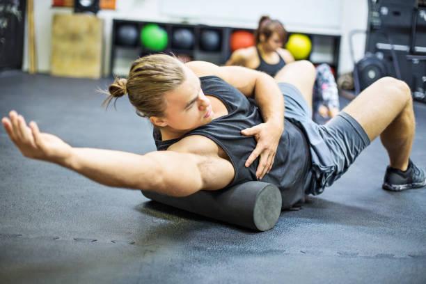Hombre haciendo ejercicio en el rodillo de la espuma en gimnasio - foto de stock