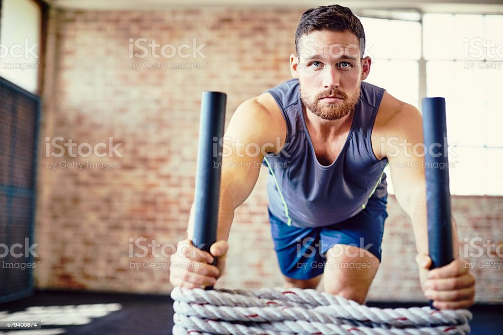 Man exercising on rope sled in training gym stock photo