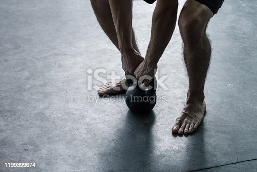 944655208 istock photo Man exercising with a kettlebell at the gym 1199399674