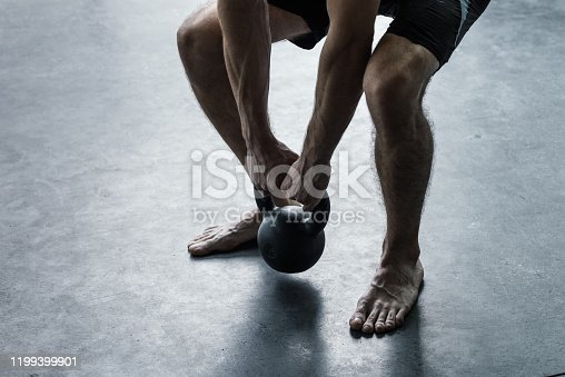 944655208 istock photo Man exercising with a kettlebell at the gym 1199399901