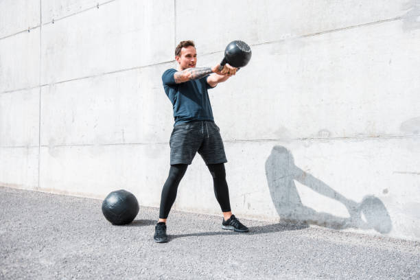 hombre haciendo ejercicio con una kettlebell al aire libre - pesa rusa fotografías e imágenes de stock