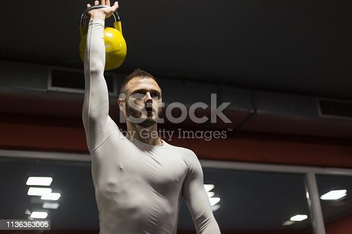 944655208 istock photo Man exercising with a kettlebell 1136363005