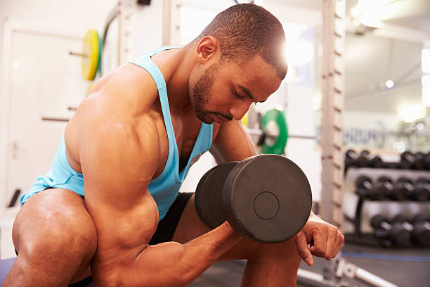 Man exercising with dumbbells at a gym, horizontal shot stock photo