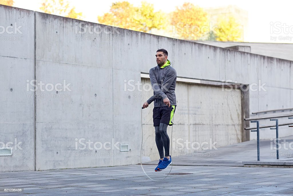 man exercising with jump-rope outdoors stock photo