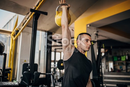 One man, fit young man exercising with kettlebell in gym alone.