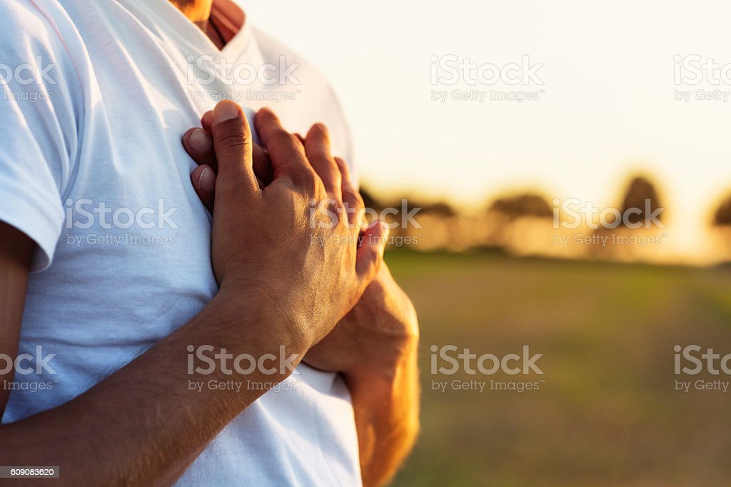 man exercising Yoga outdoors at sunset hands on chest close-up – Foto