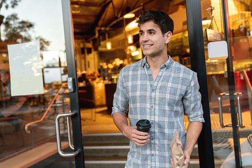 Man exiting a cafe carrying coffee to go