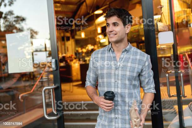 Man exiting a cafe carrying coffee to go picture id1003747594?b=1&k=6&m=1003747594&s=612x612&h=vd3yinedxbggyrry5p ruodgwpggpahf1dvjojk3fn0=