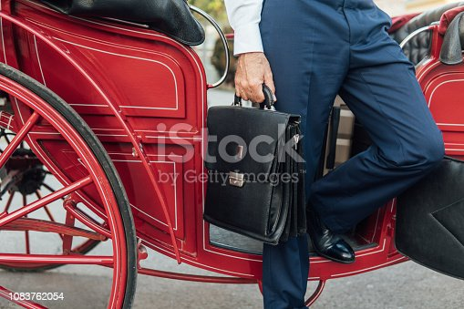 Business man stepping out of the carriage