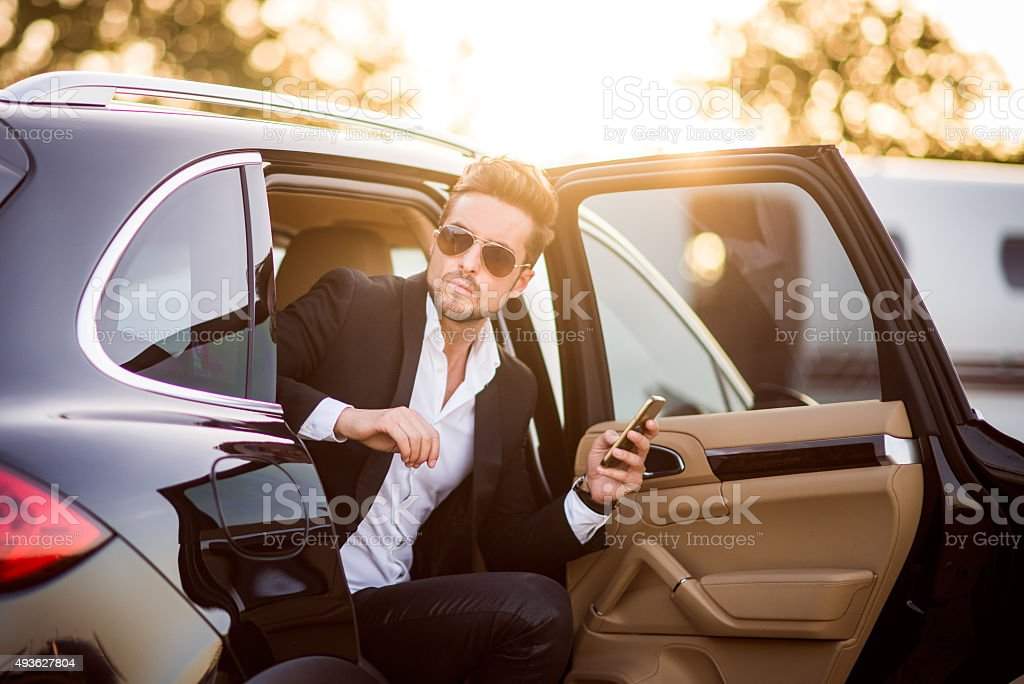 Man exiting the car with phone in his hand stock photo