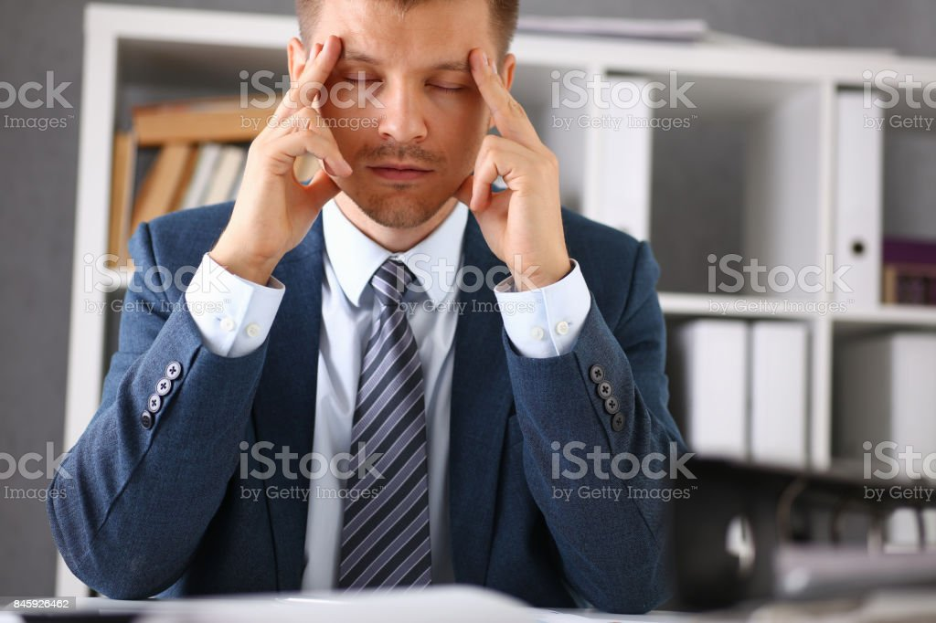 A man experiences stress and a headache in the workplace - Royalty-free Accountancy Stock Photo