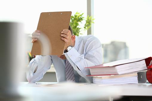 690496350 istock photo A man experiences stress and a headache 1073095536