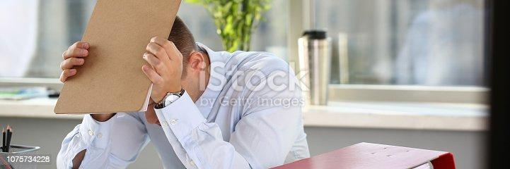 690496350istockphoto A man experiences stress and a headache 1075734228